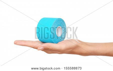 Female hand holding special physio tape roll on white background