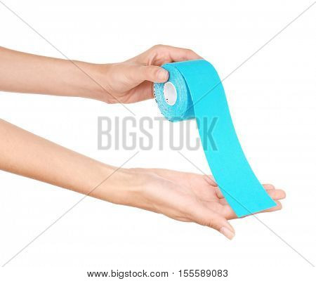 Female hands holding special physio tape roll on white background