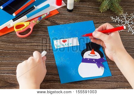 Child Paper Glued Parts That I Love Winter. The Child Makes A Greeting Card With A Snowman. Glue, Pa
