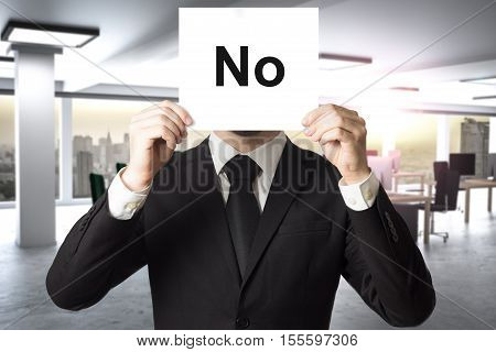 businessman in office hiding face behind sign no