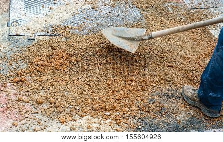 worker committed to the repair of a large pit road with inert mixed stabilized