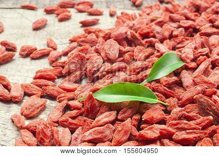 Goji. Goji berries arranged on wood. Goji berries. Goji fruits for health. Goji berries. Red dried goji berries. Goji berries with leaves.Goji berries on wooden background.