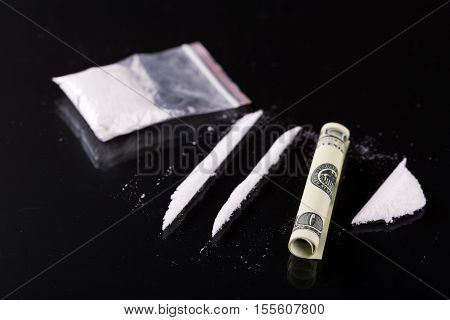 Rolled Hundred Dollars Banknote, Two Lines And Plastic Packet Of Cocaine