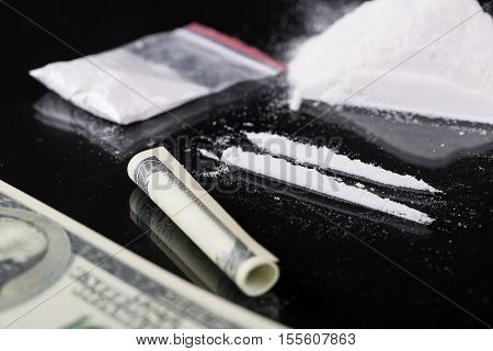 Rolled Hundred Dollars Banknote, Two Lines And Plastic Packet Of Cocaine On Black Background,