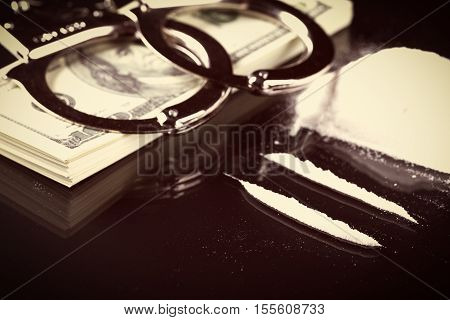 Handcuffs On Stack Of Dollar Banknotes And Cocaine
