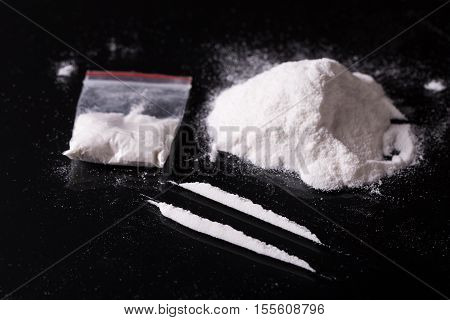 Plastic Packet, Two Lines And Pile Of Cocaine On Black Background