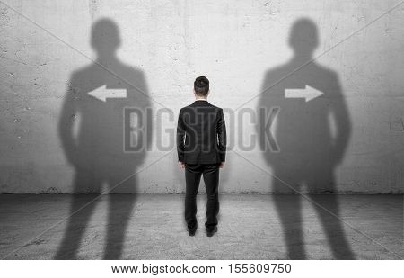 Businessman standing in front of a concrete wall with arrows pointing at different directions. Stand in front of choice. To make a decision. Difficulties of choice.