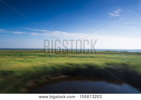 Colorful Green Gars leading to a North sea beach between coastal grasses and dunes on a sunny blue sky day conceptual of travel and a summer vacation