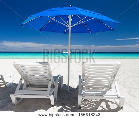 Caribbean Beach With Blue Sun Umbrellas And White Beds