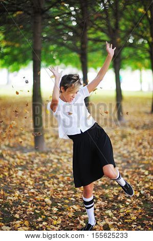 Cute young girl dancing and throwing leaves in the air in the autumn park