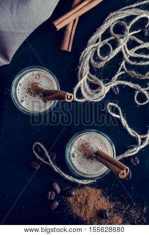 Espresso liqueur served on a table. Irish creme liqueur on dark background with coffee beans and cinnamon. Shot glass of creamy coffee liqueur with coffee beans. Alcoholic bavarage concept. Top view.
