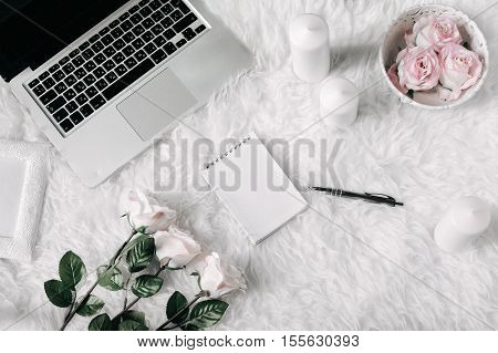Freelance fashion comfortable feminine workspace in flat lay style with laptop, vintage tray, roses, candles, notebook and pen on white fur background. Top view, flat lay. Freelance concept.