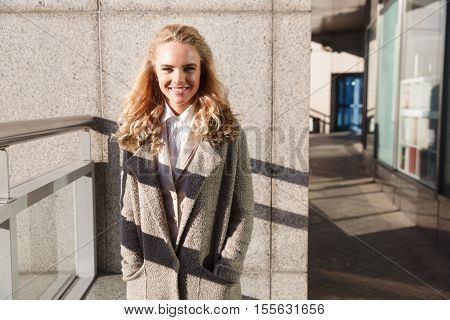 Portrait of attractive young woman in coat on porch of office building, lady smiling looking at camera