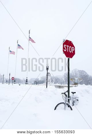 Washington D.C. USA - January 23 2016: Bike covered with snow under a stop sign