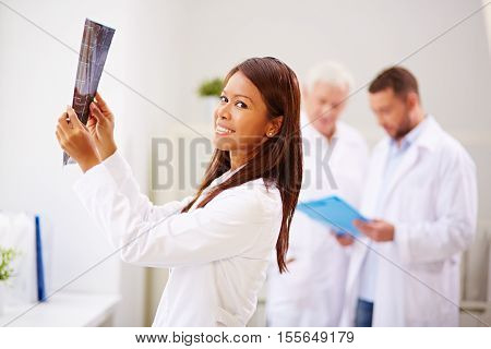 Smiling female doctor holding x-ray image, her male colleagues working in the background