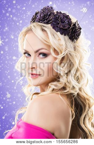 Beauty portrait of attractive blond girl with curly hair and a beautiful headband over magenta winter background. Christmas concept.