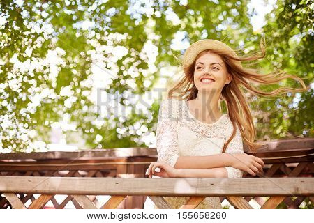 Beautiful girl leaning on wooden railing, her hair flying in the wind