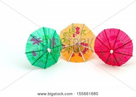 Close up colorful of many cocktail umbrellas on white background