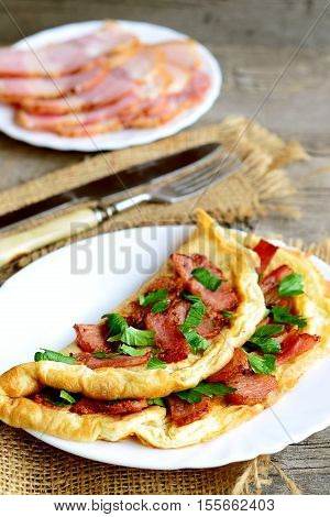 Fried bacon omelet. Tasty omelet with bacon and parsley on a plate, bacon slices on a plate, fork, knife on old wooden background. Delicious breakfast idea. Rustic style