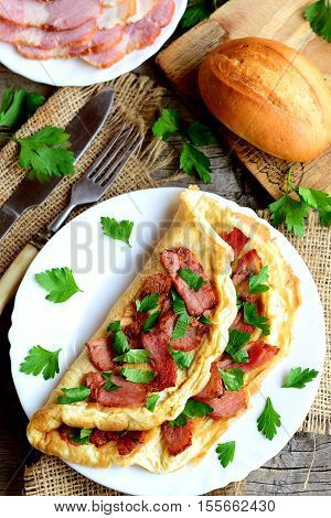 Bacon omelette recipe. Homemade omelette with bacon and parsley on a plate, bacon slices on a plate, bread roll, fork, knife, cutting board, fresh parsley sprigs on old wooden background. Top view