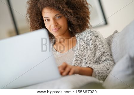 Beautiful woman at home websurfing with laptop computer