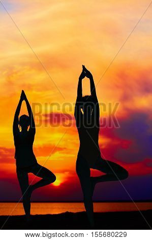 Yoga people training and meditating in warrior pose outside by beach at sunrise or sunset. Woman and man yoga exercising training in serene ocean landscape. Silhouette of couple against sun.