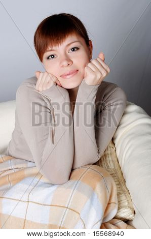 Young charming brunette in a gray jacket resting on the sofa