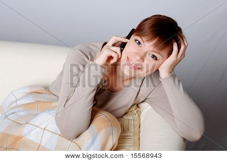 Young charming brunette in a gray jacket resting on the sofa and on the phone