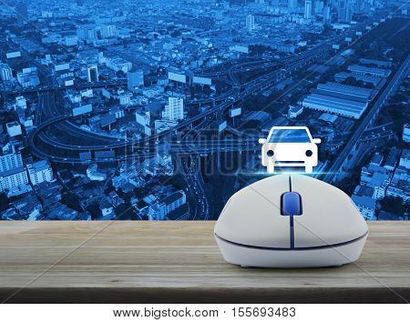 Wireless computer mouse with car front view flat icon on wooden table over aerial of city tower street and expressway Internet service car concept