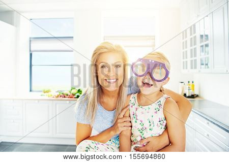 Vivacious little girl in outsized plastic glasses laughing merrily for the camera as she is hugged by her loving mother
