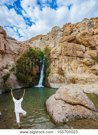 An elderly woman practices yoga on a small lake. Travel national parks and reserves Ein Gedi, Dead Sea, Israel