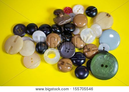 colorful buttons on yellow background, for clothes