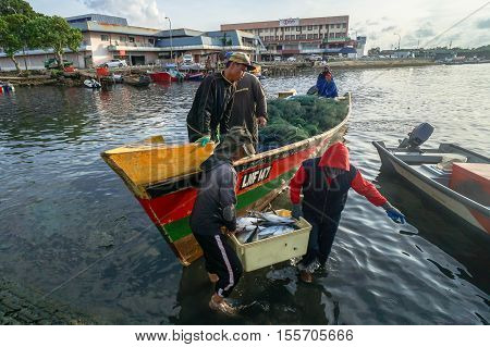 Labuan,Malaysia-Nov 9,2016:Fishermen carry their catch to the shore at Labuan island on 9th Nov 2016.The waters off the coast of Labuan islands are rich fishing grounds.