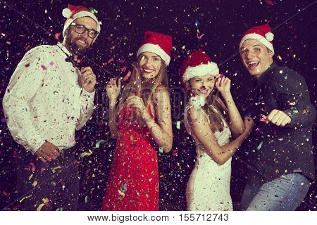 Two beautiful young couples having fun at New Year's party wearing santa's hats and dancing