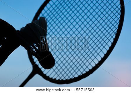 silhouette shuttlecocks on hand and racket badminton with blue sky background