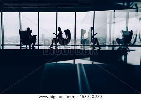 Silhouettes of two business people man and woman working on their gadgets sitting on armchairs in office interior with a lot of reflections with huge windows and winter cityscape outside
