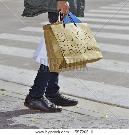 closeup of a young caucasian man outdoors carrying some shopping bags, one of them with the text black friday written in it