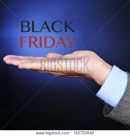 the hand of a young caucasian man wearing a gray suit and the text black friday on a black background lightened in blue