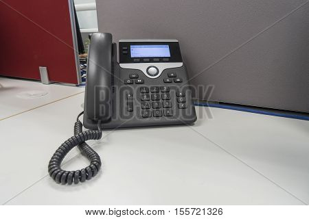 IP phone on white desk and gray partition at office - can use to display or montage on product