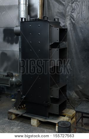 Black solid fuel boiler stands on the floor