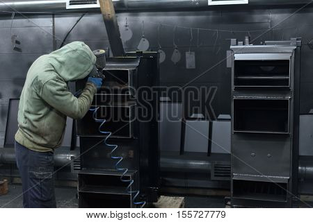 Look from behind at man working on black solid fuel boiler