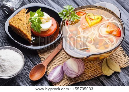 Fresh vegetable soup with noodles in a pot on the black wooden background