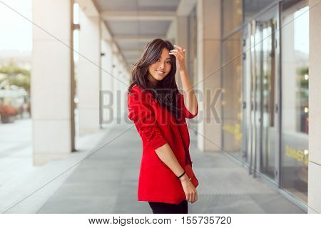 Happy asian woman standing outdoors in business casual red suite against mall
