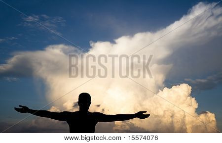 young Man open arm on clouds black silhouette