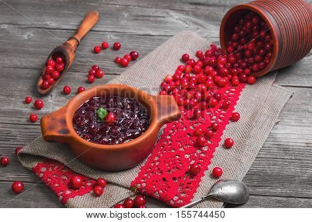 Homemade Lingonberry cranberry cowberries sauce. Fresh berries Lingonberry cranberries cowberries in ceramic cup. Lingonberry on table. Grey rustic wooden background.