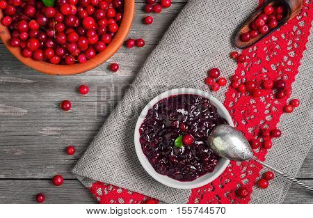 Homemade Lingonberry cranberry cowberries sauce. Fresh berries Lingonberry cranberries cowberries in ceramic cup. Lingonberry on table. Grey rustic wooden background. Top view
