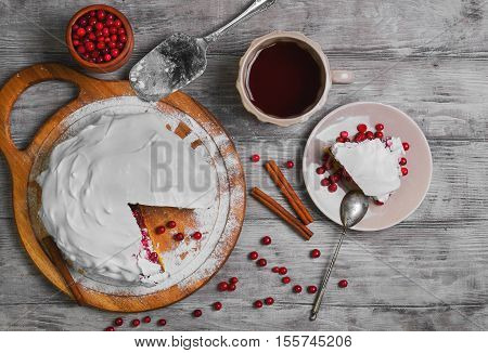 Christmas New Year winter pie cake red berry cranberries cover white whipped meringue icing tea. Slice winter Christmas pie cake on plate. Cranberry for winter pie. Light wood background. Top view