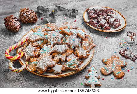 Christmas sweets baking gingerbread cookies on the plate. Forms for Christmas gingerbread cookies chocolate christmas figurines bumps. Christmas cookies gingerbread on white light table. New Year food.