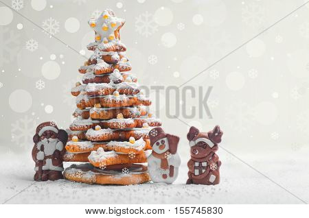 New Year Christmas card. Gingerbread Christmas tree Cookies decorated with icing sugar and sweets. Christmas Chocolate Marzipan figure next to the gingerbread Christmas tree. Sweet snow. Blank space