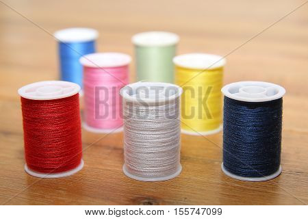 Multi-colored Cotton Reels Or Bobbins On A Wooden Sewing Table